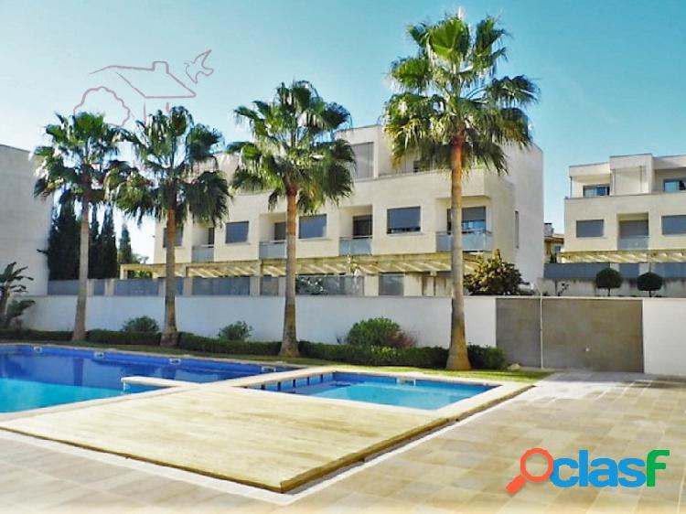 Chalet adosado de cuatro alturas con jardín y piscina comunitario en portocolom.