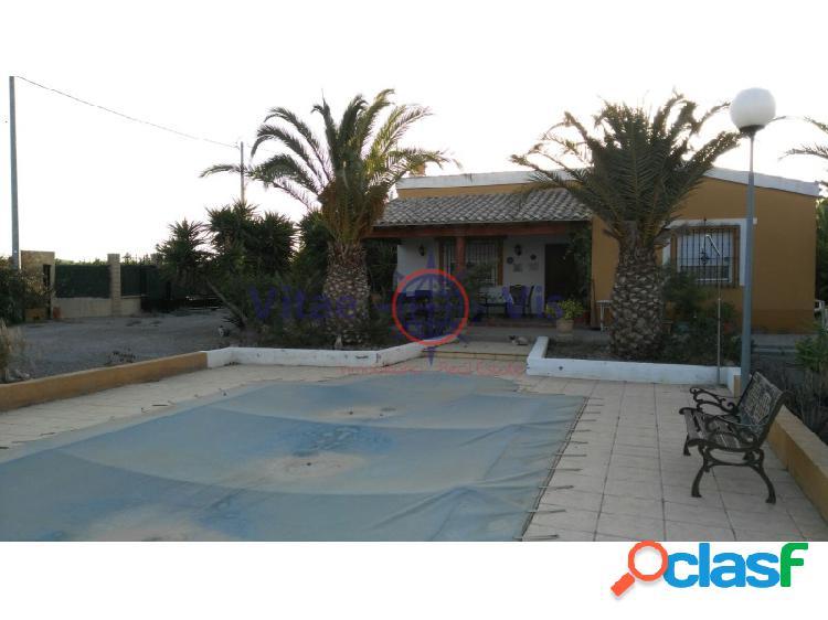 Casa con salon grande, dos dormitorios, baño, porche cubierto de 35 m2 piscina, parcela vallada con arboles frutales y olivos