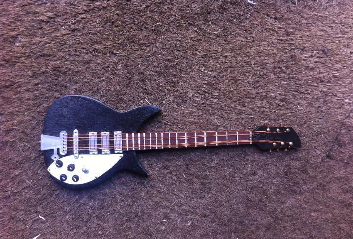 Guitarra de madera de juguete. largo: 18cm.