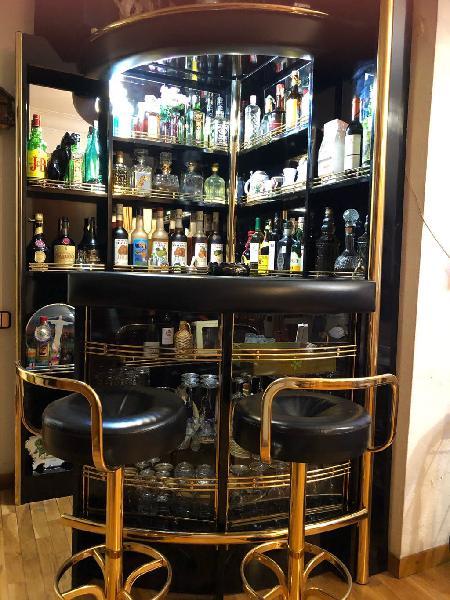 Mueble bar negro y dorado, con tamburetes y luces