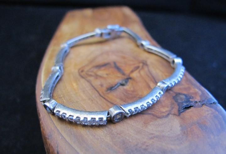 Fina pulsera de plata contrastada con piedrecitas.