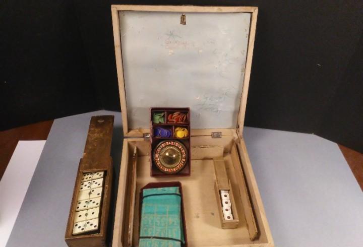 Antigua caja de juegos con dominó, ruleta y dados de