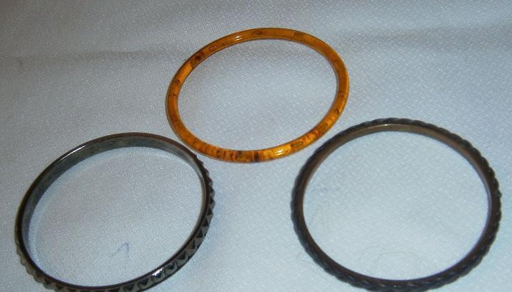 Tres pulseras una ambar y dos de metal una trabajada y otra