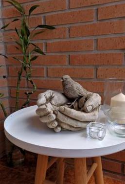 Figura de piedra pájaro en manos