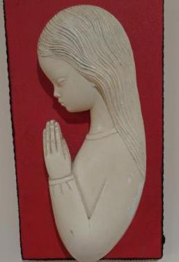 Relieve de una chica rezando.