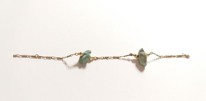 Parte de una pulsera. dorada. piedras verdes.