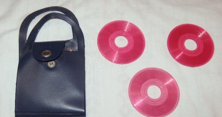 Bolso azul con tres discos de canciones de