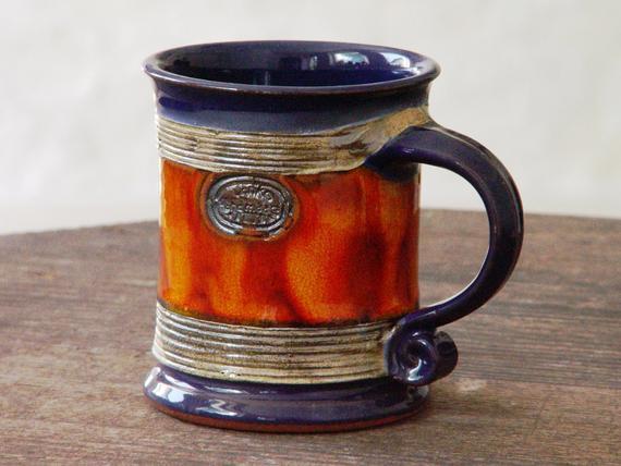 Taza de café de cerámica hecha a mano azul y anaranjada