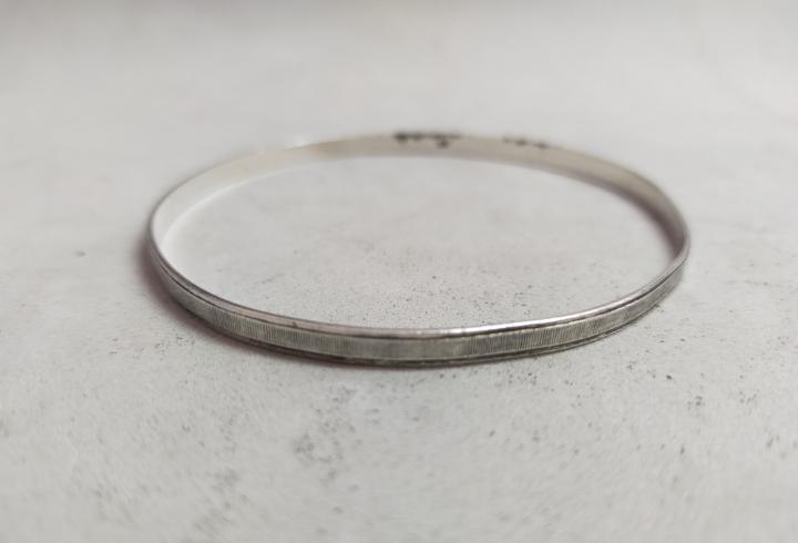 Pulsera de plata, con forma de aro, marcas en el interior